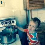 toddler standing on table and stirring stew
