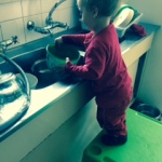 toddler stands on table and tries to wash dishes