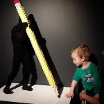 toddler with pencil lego sculpture