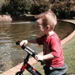 toddler on balance bike next to water