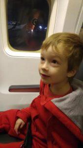 child sitting next to window of plane